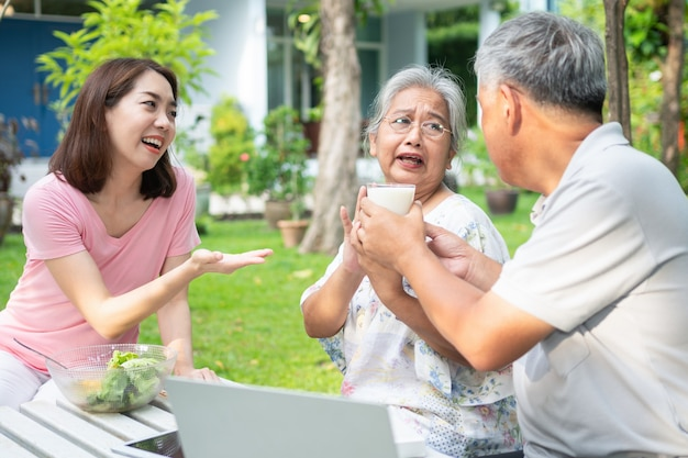 Unhappy asian senior woman anorexia and say no to meals, elderly live with family and caregivers try feed food and old woman no appetite, concept of healthcare and elderly caregivers
