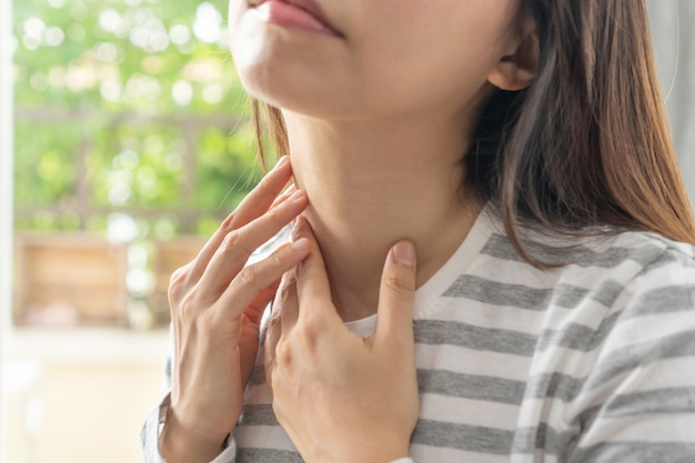 Unhappy asian woman having sore throat, feeling sick. ill girl suffering from painful swallowing, strong pain in throat, hand touching on her neck at home. health problems concept.