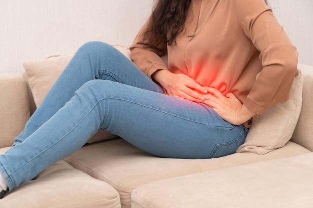 불행한 아시아 여성은 소파에 앉아서 고통을 안고 있습니다. 월경, 설사 또는 소화 불량으로 인한 복통. 질병 및 건강 관리 개념