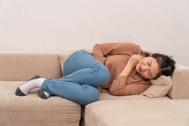 불행한 아시아 여자는 소파에 앉아 위장 고통에 들고.