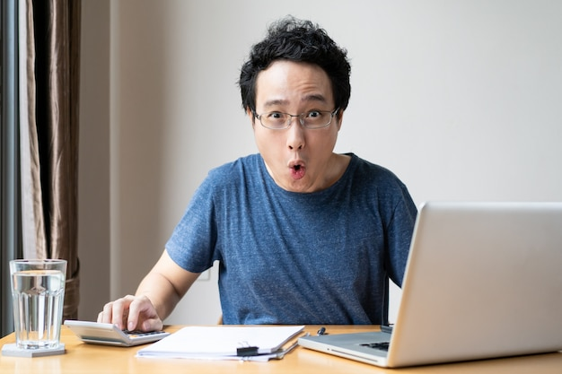 Unhappy asian young man working at his home portrait. uncomfortable working space is not good for employee. stressful asian man.