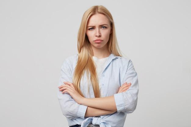 Infelice donna bionda attraente in piedi con le braccia incrociate, guardando triste e andando a piangere, indossando abiti casual