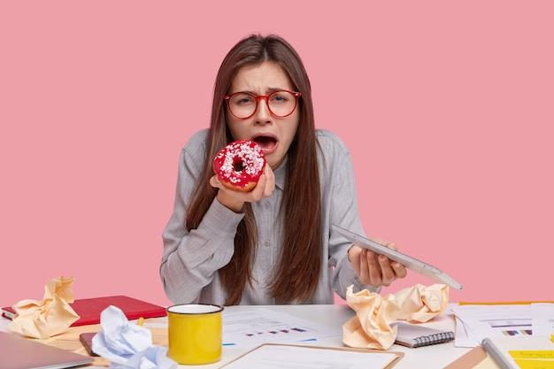불행한 매력적인 젊은 여성이 직장에서 문제가 있고, 맛있는 달콤한 도넛을 먹고, 현대적인 터치 패드를 들고, 비즈니스 전략을 개발하고, 그래프를 연구하면서 울고 있습니다.