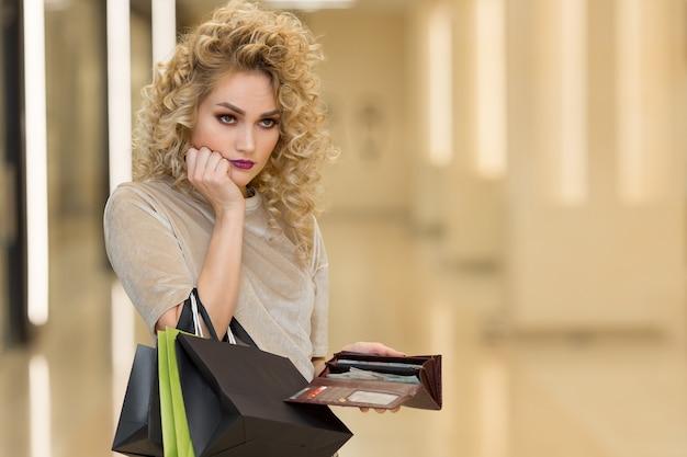 空の財布を持つ不幸な破産した女性。若い女性は彼女の空の財布を示しています。倒産