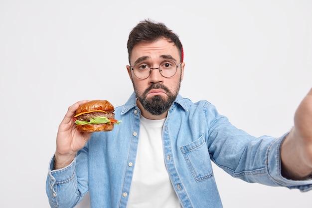 불행한 수염 난 성인 유럽인 남자가 정크를 먹고 맛있는 햄버거를 먹고 셀카 지갑을 만듭니다 입술에 불만이 있습니다 표정이 둥근 안경 데님 셔츠를 입습니다.