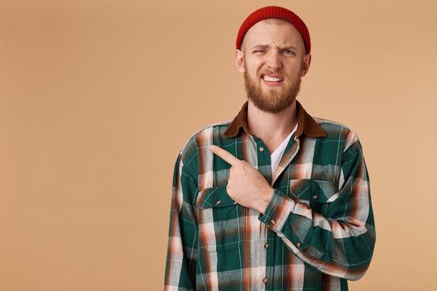 Infelice maschio barbuto con cappello rosso senza punti di piacere con il dito indice nell'angolo sinistro