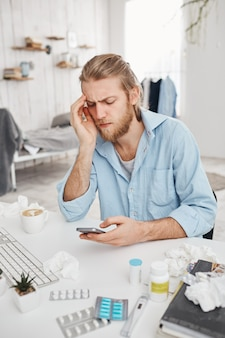 Unhappy bearded young male manager sitting at table surrounded by pills, tablets, drugs. fair-haired office worker has bad cold, surfes internet, suffers from high temperature. health problems.