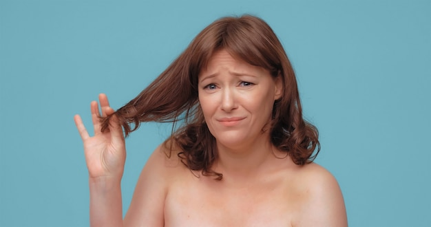Unhappy beautiful woman holds of hair ends looking at camera pretty nude mature woman on color back ...