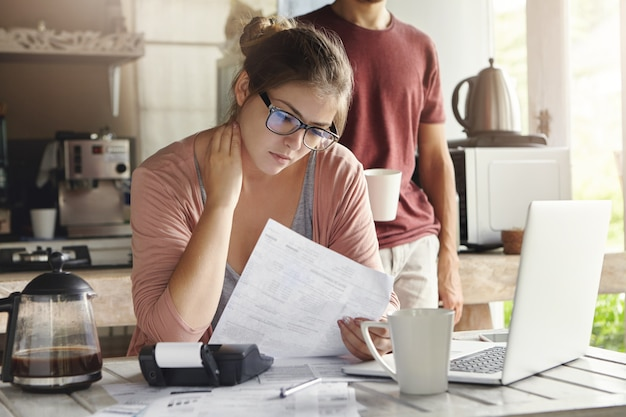 Unhappy beautiful woman wearing spectacles having concentrated look reading notification form bank on debt, sitting at kitchen table in front of open laptop