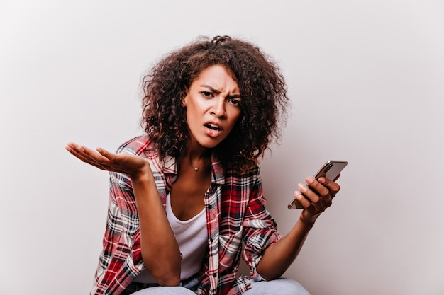 白でスマートフォンを保持している不幸な黒人の女の子。赤いシャツを着た無愛想なアフリカの女性