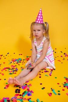 散乱紙吹雪で退屈な顔をして不幸な金髪白人少女。黄色のスタジオの背景。悪い誕生日パーティー。