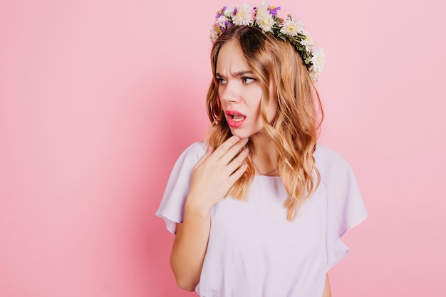 Donna bionda infelice in corona di fiori che guarda lontano