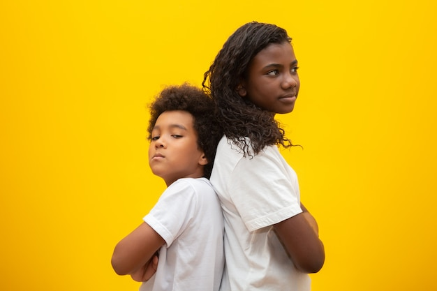 Unhappy brother and sister. young brothers standing back to back with arms folded over yellow .