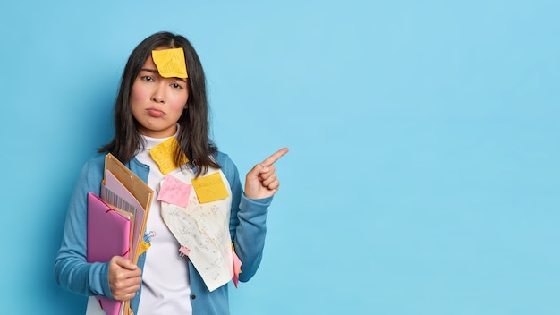 Unhappy brunette asian woman holds folders with papers gives recommendations how to prepare for exams has sticker on forehead indicates at copy space Free Photo