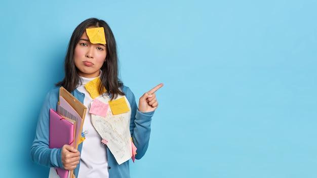 Несчастная брюнетка азиатская женщина держит папки с бумагами, дает рекомендации, как подготовиться к экзаменам, имеет наклейку на лбу, указывает на место для копирования