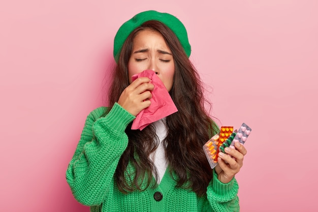 Unhappy brunette girl suffers from flu symptoms, rubs nose with handkerchief, has cold, holds pills, wears green jumper and cap, isolated on pink wall