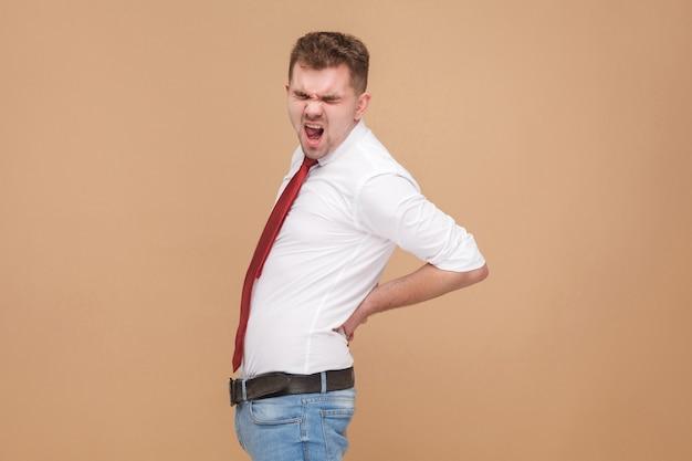 不幸なビジネスマンは背骨の痛みや腎臓の病気を持っています