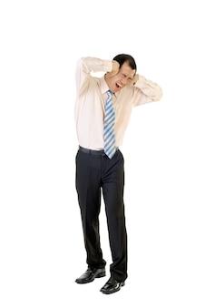 白い背景の上に立っているストレスの下でアジアの不幸な実業家。