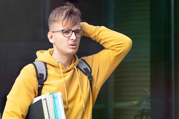 不幸な忙しさは悲しい絶望的な男、欲求不満の若い大学生や大学生、眼鏡をかけた生徒、本や教科書で苦しんでいるバックパックを強調しました。過労、重い作業負荷。過労のコンセプト