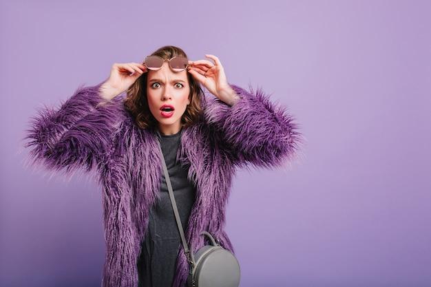 Infelice ragazza caucasica in soffice pelliccia in posa su sfondo viola