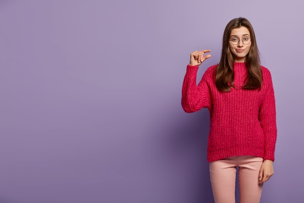 불행한 백인 아가씨는 작은 제스처를 만들고, 작은 것을 보여주고, 불행한 표정을 짓고, 보라색 벽 위에 고립 된 빨간색 점퍼와 바지를 입습니다. 사람과 크기 개념