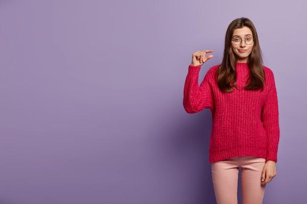 La signora caucasica infelice fa un piccolo gesto, dimostra qualcosa di minuscolo, ha un'espressione infelice, indossa un maglione e pantaloni rossi, isolato su un muro viola persone e concetto di taglia
