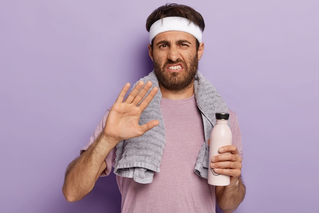 Unhappy caucasian man refuses to participate in sport competition, makes rejection gesture, holds bottle of water, has cardio training in gym wears headband and t shirt. sip of freshness after workout