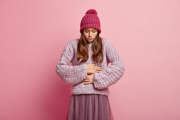 Unhappy caucasian woman keeps both hands on belly, ate spoiled food, has unpleasant feeling in stomach, wears pink headgear with pompon, knitted jumper and pleated skirt, stands over pink wall