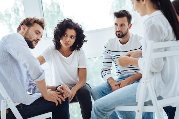 그룹 치료 세션을 갖는 동안 서클에 앉아 문제를 해결하려고 노력하는 불행한 쾌활한 슬픈 사람들