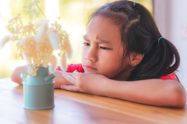 Unhappy child girl is looking at a dry flower vase