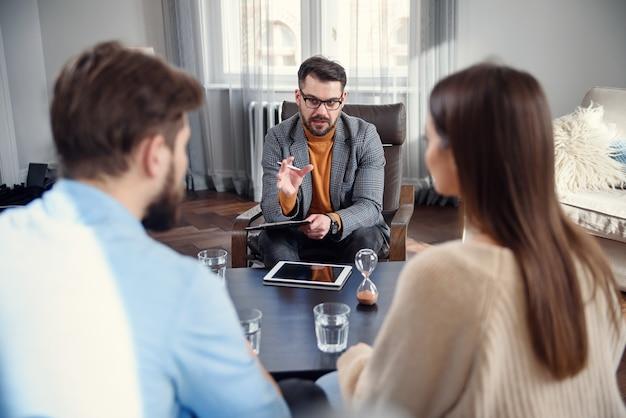 不幸な夫婦が主張し、戦い、心理学者のオフィスで意見の相違があり、セラピストとの関係の問題について話し合っている欲求不満の若い家族