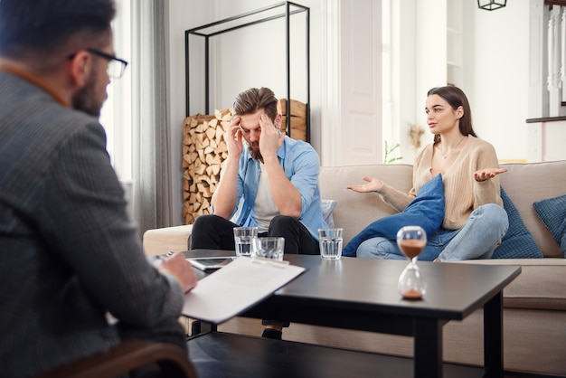 Несчастная пара, спорящая, драки, разногласия в офисе психолога, разочарованная молодая семья, обсуждающая проблемы отношений со своим терапевтом