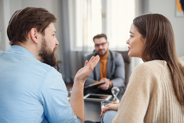 Unhappy couple arguing, having fight, disagreement at psychologists office, frustrated young family discussing relationship problems with their therapist
