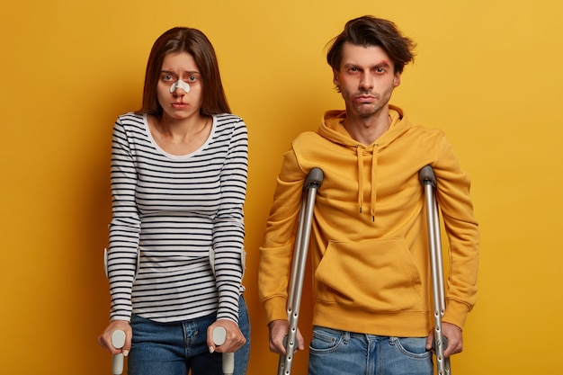 Unhappy couple got into accident, suffer from painful feelings and various traumas, stand next to each other on crutches, isolated on yellow wall. accident insurance and medical concept