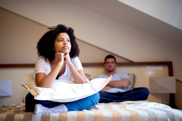 Unhappy couple sitting on bed after argument. looking sad and annoyed