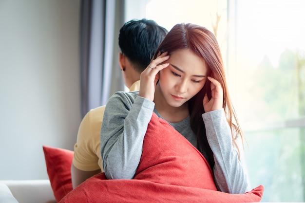 不幸な夫婦がソファでお互いの後ろに座って、話を避けます