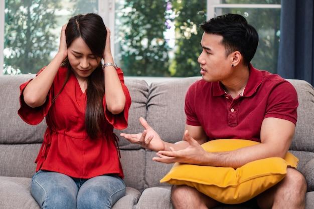 Несчастная пара сидит рядом на диване и избегает разговоров или ссор