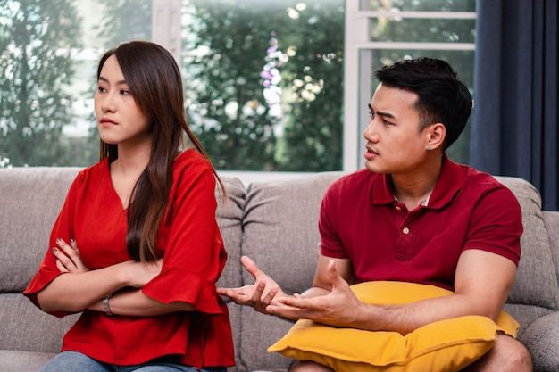 Несчастная пара сидит рядом на диване и избегает разговоров и ссор