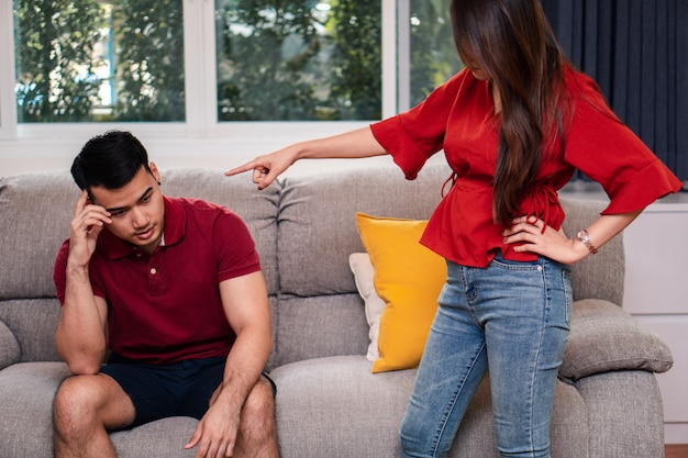 Unhappy couple sitting beside each other on the sofa and avoid talking or quarrel.