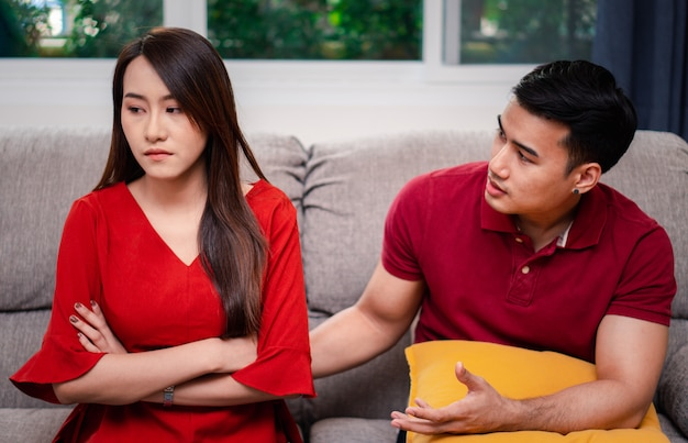 Unhappy couple sitting beside each other on the sofa and avoid talking or quarrel