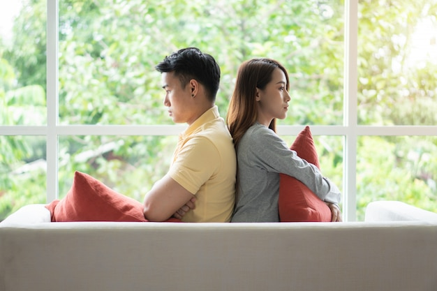 Unhappy couple sitting behind each other on the couch and avoid talking