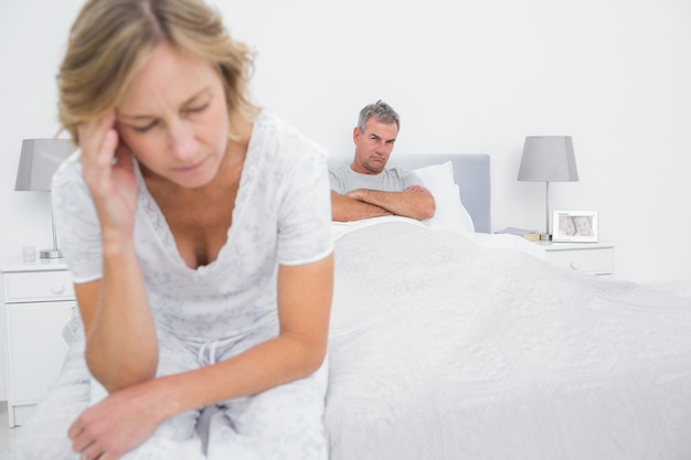 Unhappy couple sitting on opposite ends of bed after a fight
