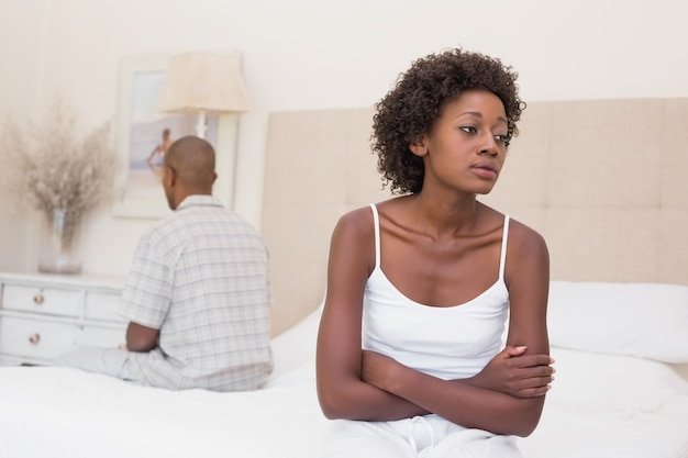 Unhappy couple not speaking to each other on bed