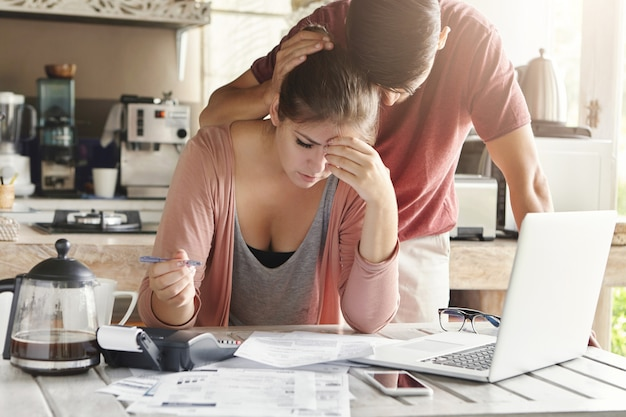 Unhappy couple unable to pay loan on time: stressed female doing paperwork sitting at table with laptop, papers, calculator and cell phone. man trying to support his wife