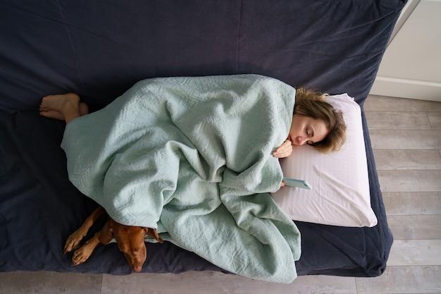 불행한 우는 여자는 개와 담요로 덮인 소파에 누워 있는 전 남자친구의 메시지를 읽었다