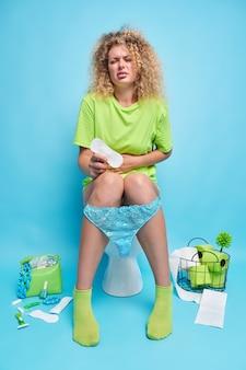 Несчастная кудрявая молодая женщина держит живот, чувствует дискомфорт во время менструации, страдает от спазмов в животе, держит чистую гигиеническую салфетку, позирует на сиденье унитаза у синей стены