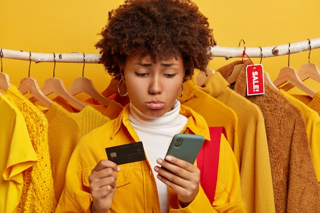 Unhappy curly woman uses credit card and smartphone for online shopping sad