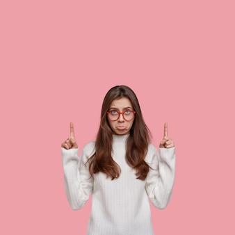 Infelice donna carina indica con le dita anteriori verso l'alto, delusa da qualcosa di negativo, vestita con abiti casual, porta il labbro inferiore con disperazione
