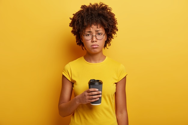 Unhappy dark skinned student holds disposable cup of caffeine beverage