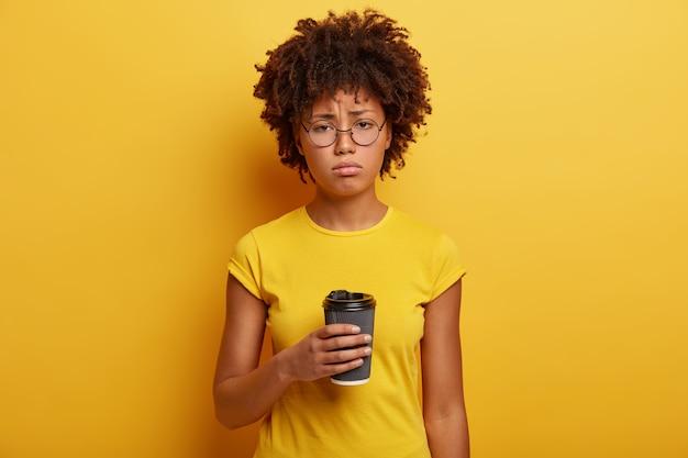 不幸な浅黒い肌の学生は、カフェイン飲料の使い捨てカップを保持しています